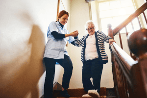 elderly woman on stairs with therapist